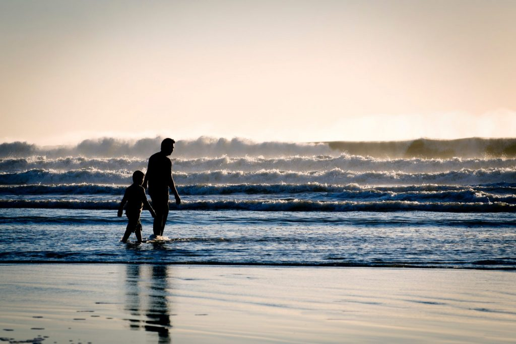 A man walking on a beach with son
